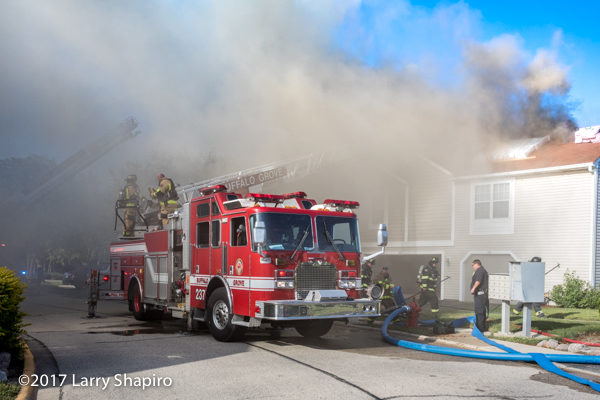 heavy smoke from townhouse fire engulfs fire truck