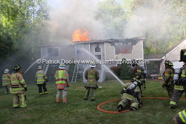 firefighters battle house with flames through the roof