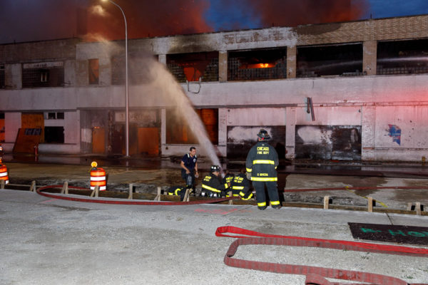 firefighters use ground nozzle at fire scene