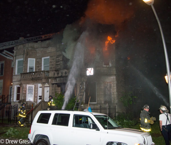 firefighters battle second floor fire at night