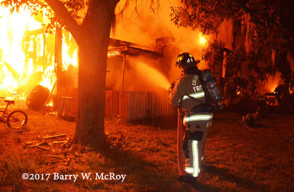 firefighter battles rural house fire with hose