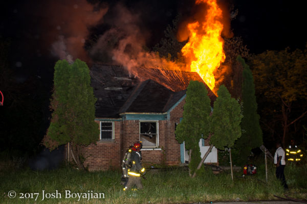 flames through roof of a vacant house