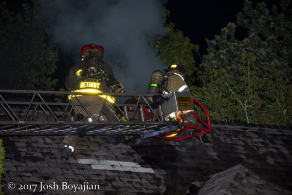 firefighters on aerial ladder tip