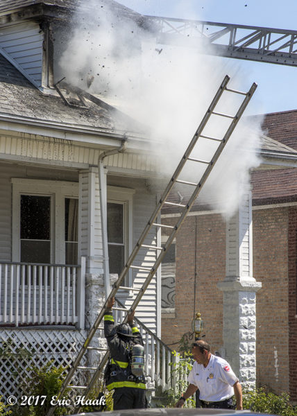firefighters raising a ground ladder at a fire