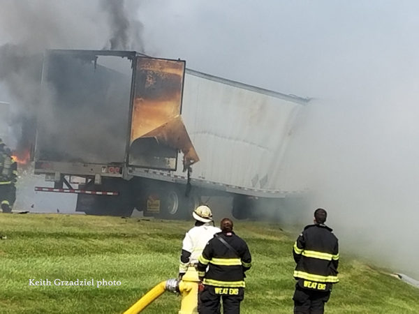 firefighters battle a tractor-trailer destroyed by fire