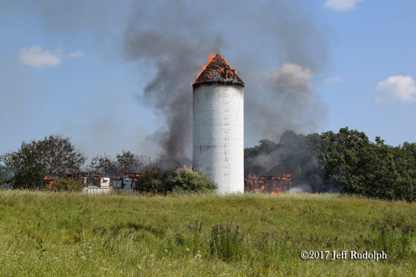 silo stands amid barn destroyed by fire