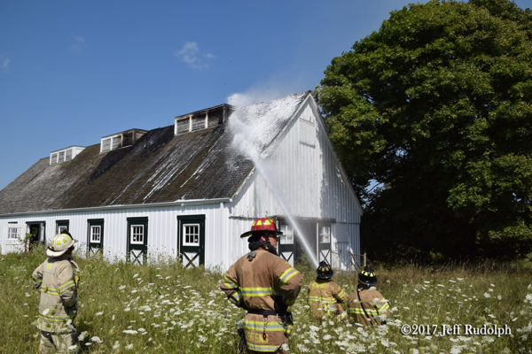 Firefighters apply foam to protect barn