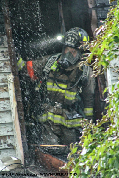 firefighter overhauls after house fire