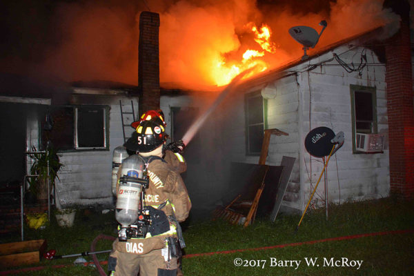 firefighters operate a hand line battling a house fire