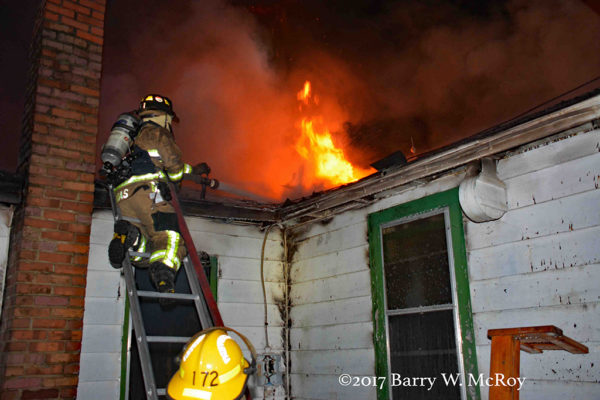 firefighters on ladder battle house fire