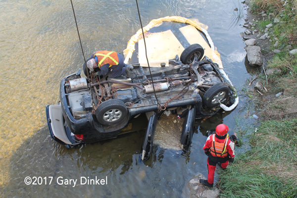 tow truck lifts car from water