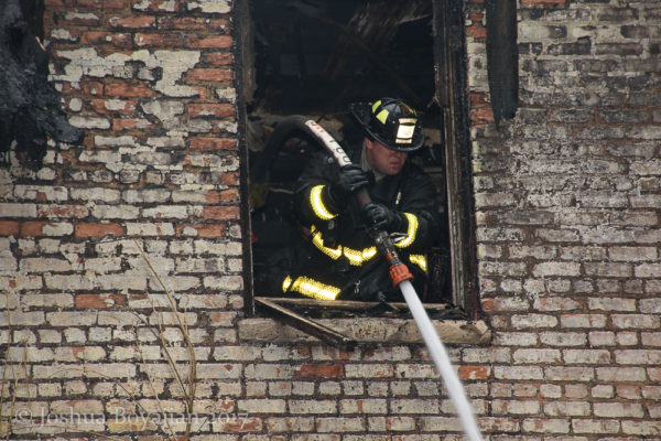Firefighter with hose line after a fire