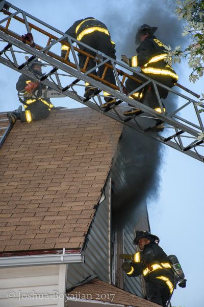 Firefighters vent roof of house on fire