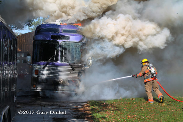 Firefighter battles tour bus fire