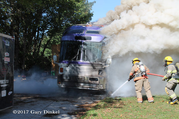 Firefighters battle tour bus fire