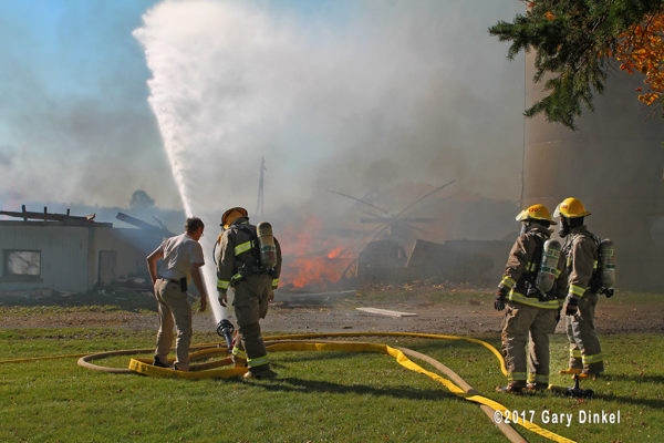 firefighters with deluge gun at barn fire