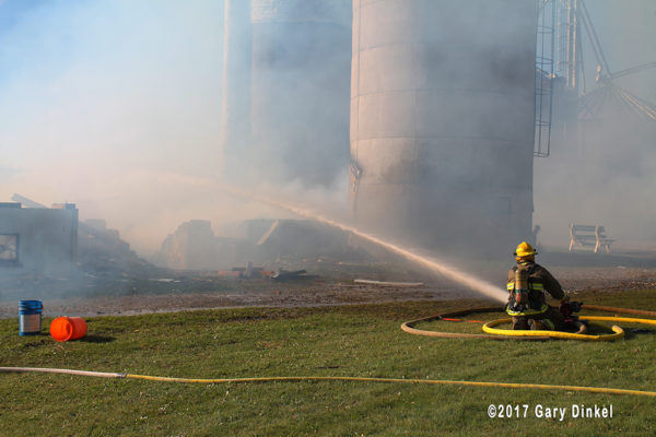 firefighters with hose line at barn fire