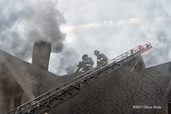 Firefighters vent house roof during a fire