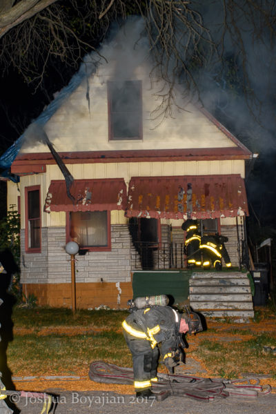 Detroit firefighters make entry into a burning house
