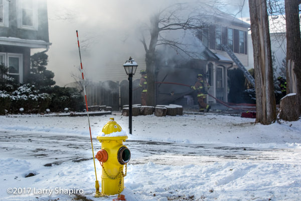 frozen fire hydrant in front of house on fire