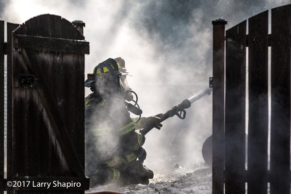firefighters operate a hose line cathouse fire