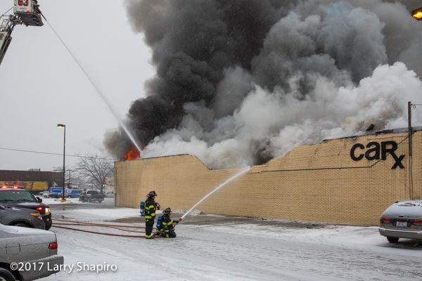 massive smoke and flames from commercial building fire with wall collapse