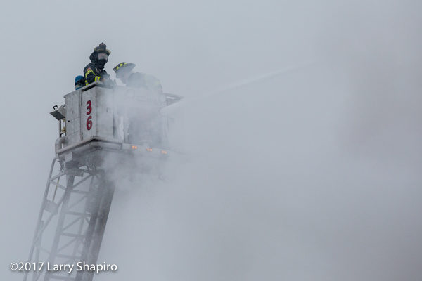 firefighters in tower ladder basket and smoke