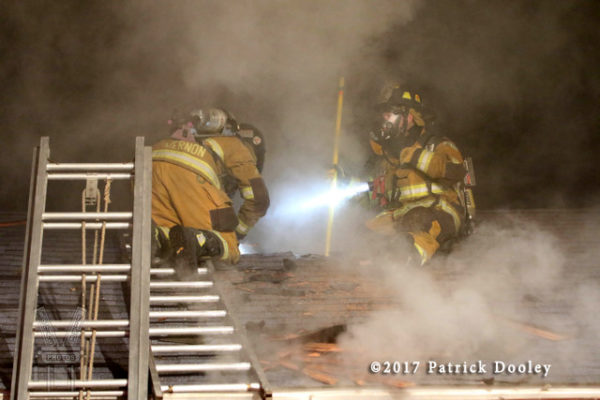 firefighters vent roof at night