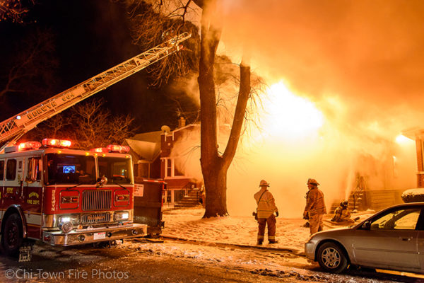 house fully engulfed in flames at night