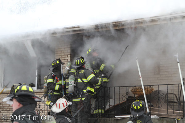 firefighters on front porch with smoke