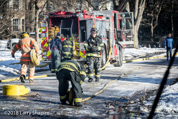 firefighters pickup hose after a fire