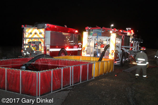 fire engines drafting from portable tanks at night
