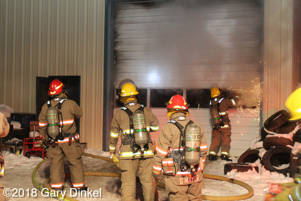 firefighters remove overhead door at fire