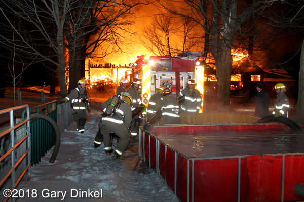 firefighters prepare to draft water at a fire