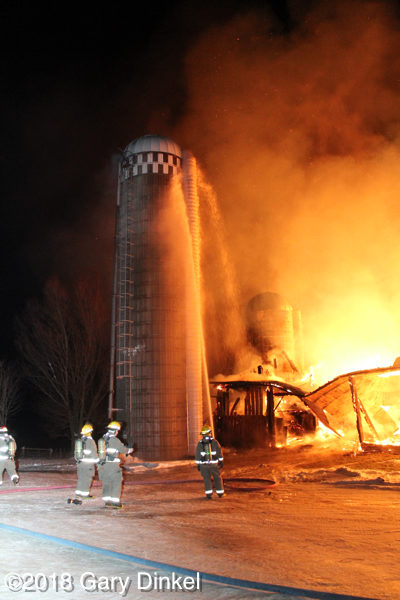 firefighters battle a barn fully engulfed in fire at night