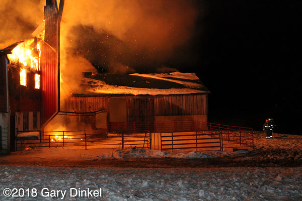 barn fully engulfed in fire at night