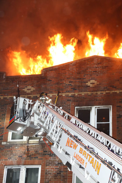 heavy flames from roof of building at night