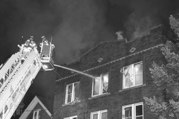 apartment building fire at night with elevated master stream