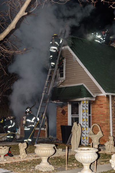 Firefighters ladder a house on fire