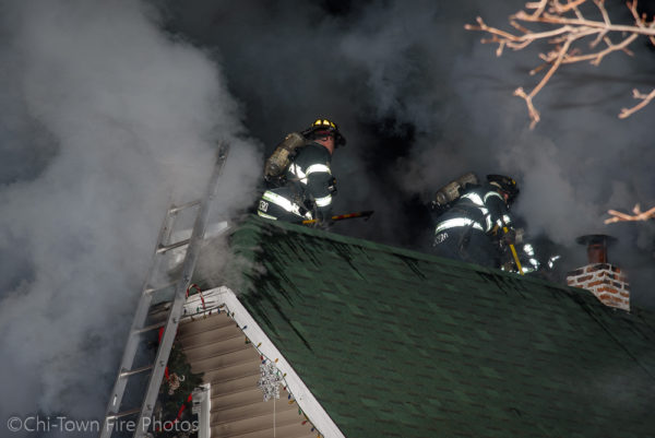 Firefighters on the roof at night with smoke