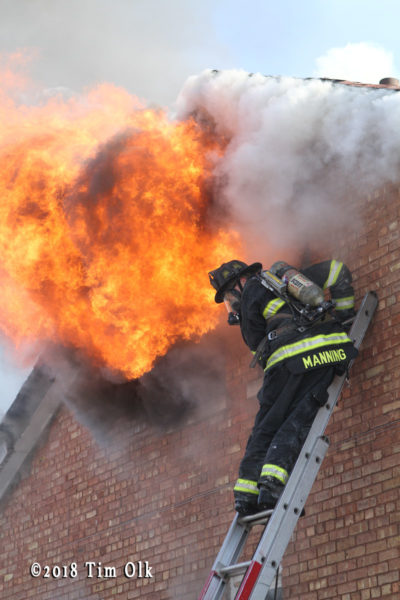firefighter on ladder with flames