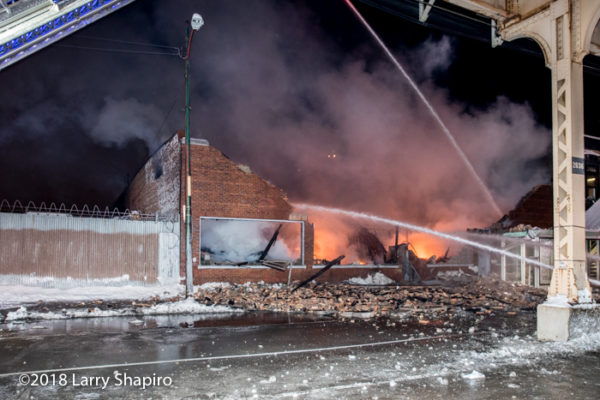 Firefighters pour water on building fire
