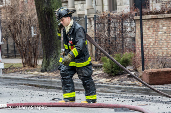 firefighter pulls hose at fire scene