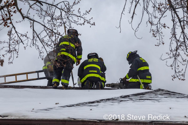 Firefighters on roof with snow