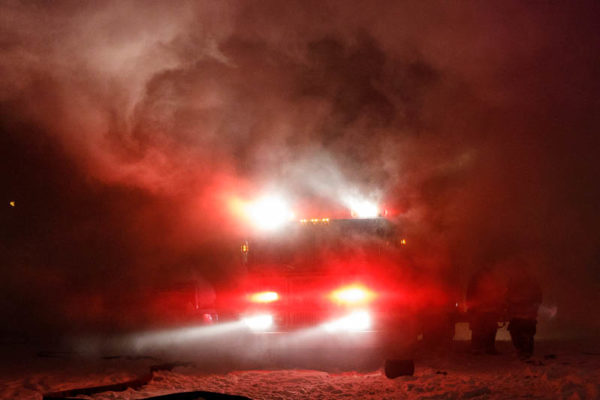fire truck with lights in smoke at night