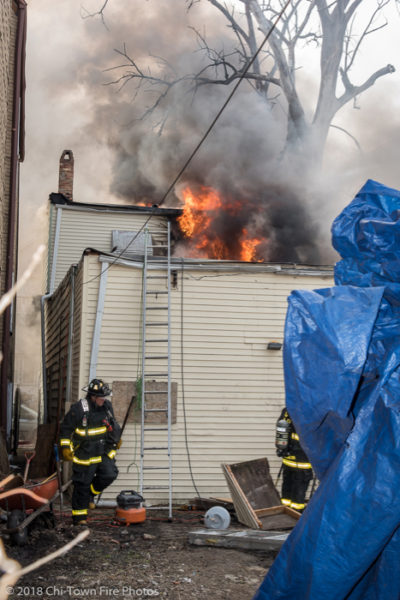 flames shoot from the roof of a house