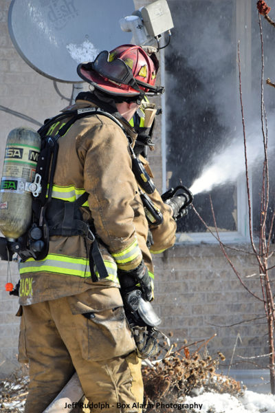Firefighters operate a hose line during a house fire