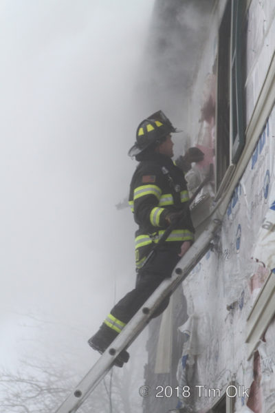 Firefighter on ladder in smoke