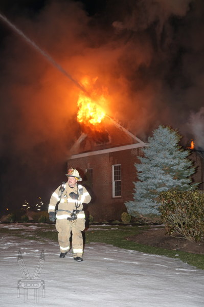 Firefighter at house fire with big flames