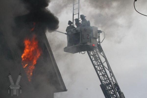 Firefighters battle fire from tower ladder